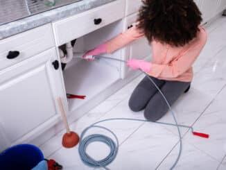 Junge Frau reinigt Rohr mit Spirale