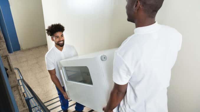 2 Männer tragen einen Schrank